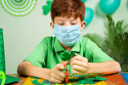 Young kid busy in preparing shamrock leaves for saint patricks day festival celebrations at home with face mask during pandemic