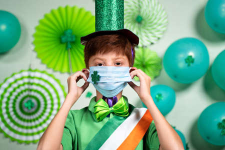 Portrait of young kid wearing medical face mask with shamrock sticker as  safety measures during saint Patricks day festival celebration