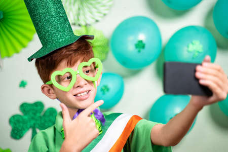 Young kid on video call during saint patricks day celebration on mobile phone and showing decorated background over video call 免版税图像