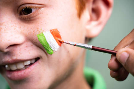 Close up of hands painting saint patricks day tricolour Irish flag on kids face during festival celebration preparations