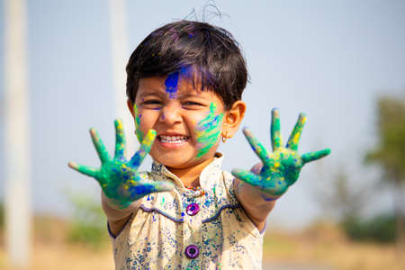 young cute cheerful little girl kid with applied holi colors powder showing colorful hands to camera during holi festival celebration