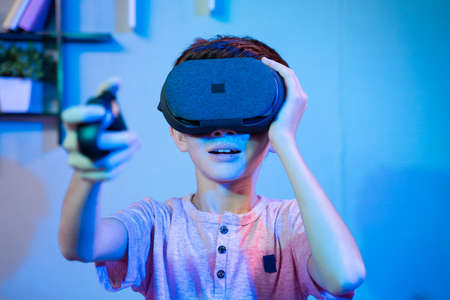 Young kid playing game by wearing vr or virtual reality headset and game pad while sitting on sofa. 免版税图像