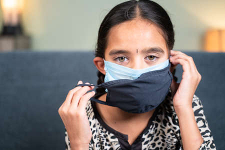 Young little girl wearing double or two face mask to protect from  outbreak - concept of safety, healthcare, medical and hygiene. 免版税图像
