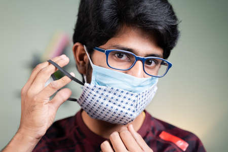 Young man wearing double or two face mask to protect from outbreak - concept of safety, healthcare, medical and hygiene.