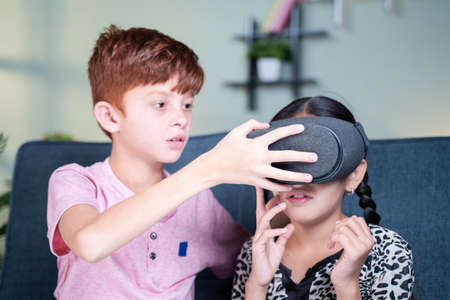 Young kid helping his sister to wear VR or virtual reality headset at home - concept of togetherness, bonding and use of technology 免版税图像