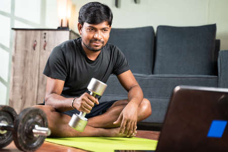 Young man busy learning how to use dumbbells through online tutorials by seeing laptop at home 免版税图像