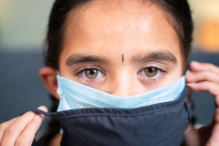 Close up head shot of girl wearing double or two face mask to protect from outbreak - concept of safety, healthcare, medical and hygiene.