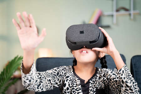 Young girl kid with VR or virtual reality goggles feeling or enjoying the 360 degree virtual environment at home - Concept of showing modren VR technology in modern lifestyle 免版税图像
