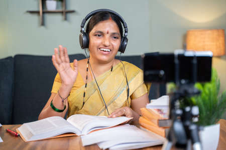 Indian woman greeting students in front of mobile during virtual online class at home - concept of new normal education, e-teaching, technology .
