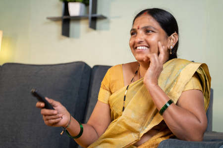 Indian woman in saree watching TV at home while sitting on sofa by holding remote during leisure time