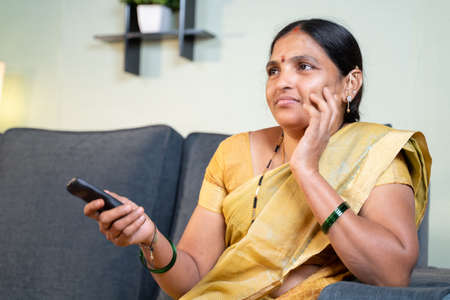 Serious Indian woman in saree watching TV serials at home while sitting on sofa by holding remote during leisure time 免版税图像