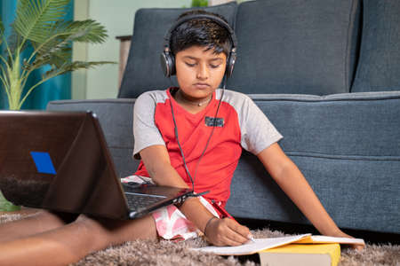 kid with headphone noting down to book from laptop during virtual class from laptop at home - concept of online classroom, online education, technology and lifestyle.