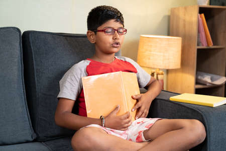 young kid mugging up answers from book during exams with out understanding the concepts at home on sofa - concept of education system and teenager kids lifestyle.