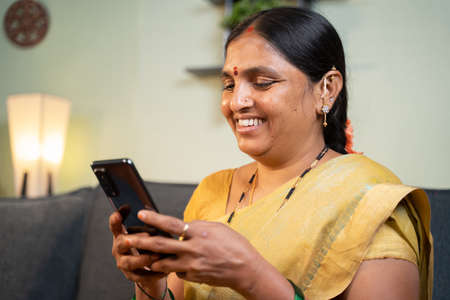Happy smiling Indian woman busy using mobile phone while sitting on sofa - Concept of people using social media, online messaging app, Internet and entertainment lifestyle.