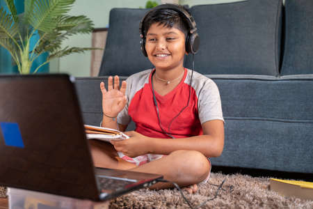 Young kid with headphones and books in handphone greeting his tutor during online class on laptop at home - Concept of Virtual education. 免版税图像