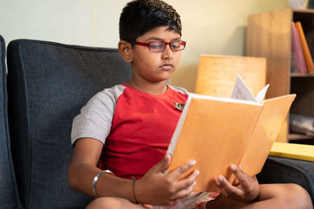 Young kid busy reading from book for exam at home - concept of education and teenager kids lifestyle.
