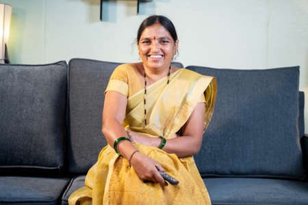 Indian woman in saree watching TV at home while sitting on sofa by holding remote during leisure time at home.