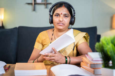 Indian woman busy explaining from book during online class by looking camera at home - Concept of e-teaching, Remote learning, virtual education