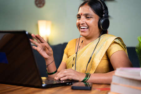 Happy Indian woman with headphones busy talking in video call on laptop - concept of online chat, distance webinar, video conference during work from home