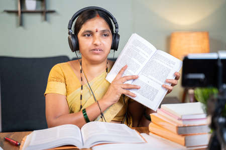 Indian woman busy explaining from book during online classing in font of mobile phone - Concept of e-teaching, Remote learning, virtual education.