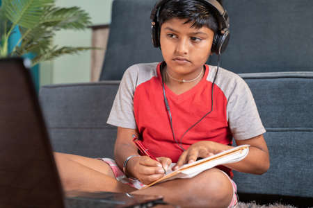 Serious kid with headphone noting down to book by seeing laptop during online class at home - concept of online classroom, online education, technology and lifestyle. 免版税图像