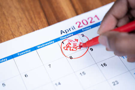 Close up hands writing and marking April fools day on 2021 calendar 免版税图像