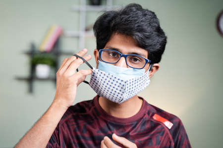 Portrait Young man wearing double or two face mask- concept of safety, healthcare, medical and hygiene.