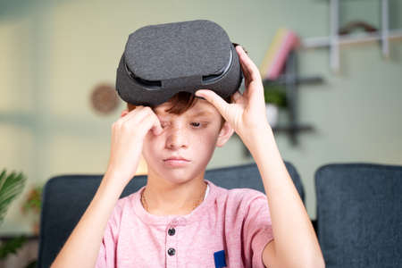 Concept showing of over use of VR or virtual reality console - Young kid rubbing his eyes after using of VR headset.