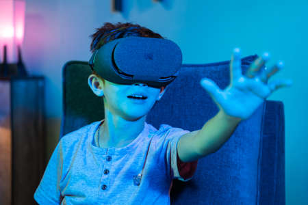 Young kid with VR or virtual reality headset feeling or enjoying the 360 degree virtual environment - Concept of showing futuristic of modern VR technology in modern lifestyle 免版税图像