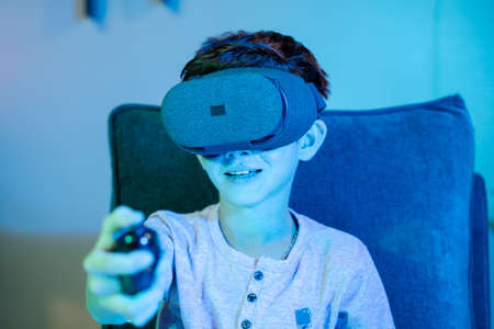 Young kid playing game by wearing vr or virtual reality headset and game pad while sitting on sofa showing with neon light effect 免版税图像