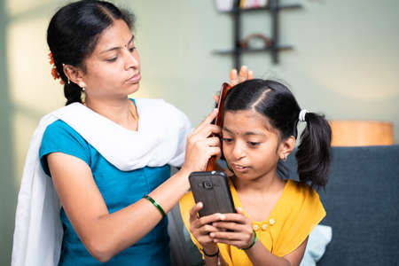 Mother combing her kid hair while kid busy using mobile home while sitting on sofa at home by ignoring mother - Concept of Kids mobile phone, game and technology addiction 免版税图像