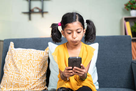 Young girl kid using mobile phone while sitting on sofa in bending head posture - concept of Kid mobile phone game addiction, technology and modern lifestyle