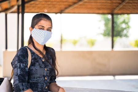 Young Indian girl with medical face mask looking camera at college campus with copy space