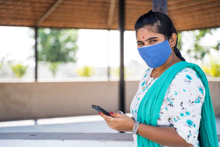 Young Indian girl with medical face mask looking camera while busy using mobile phone at college campus with copy space