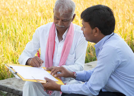 Selective focus on farmer, Banker or corporate officer getting sign from farmer while sitting near the farmland - concept of cotract farming, business deal and farm loan approval