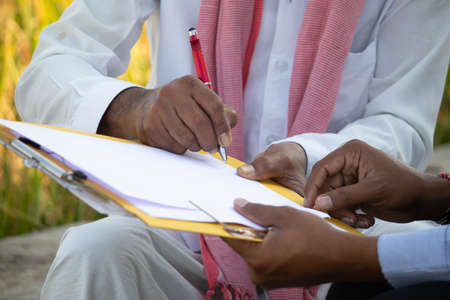 Selective focus on farmer hands, Close up of farmer hands signing on documents while sitting near the farmland - concept of cotract farming, business deal and farm loan approval