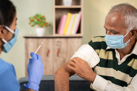 After Doctor giving vaccination shot to elderly patient by syringe or injunction, patient rubbing his shoulder at home 免版税图像