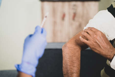 close up hands of Doctor hands given vaccination shot to elderly patient by syringe or injunction, patient rubbing his shoulder at home