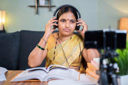 Indian woman preparing for online class by wearing headphone in front of mobile phone at home - Concept of virtual education and new normal lifestyle