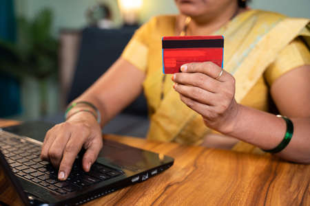 unrecognizable Indian woman hoilding credit card and entering card details into laptop for online e-commerce shopping or bill payment at home