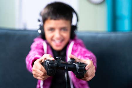 Close up selective focus on joystick, kid enjoying videogame using gamepad at home while sitting on sofa