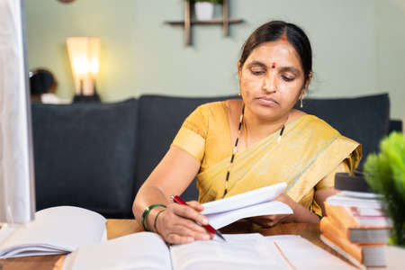 Indian woman professor correcting answer sheets of books by referring books at home at working desk