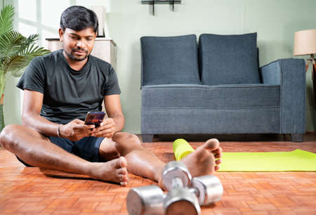 wide angle shot of Young man busy using mobile phone during work out at home - Millennial checking online exercise tutorials for workout.