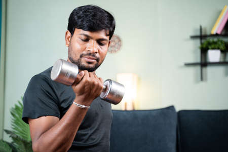 Young man in work out or doing exercise using dumbbell at home - concept of home gym