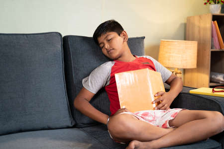 Tired kid sleeps while busy reading book for examination on sofa - concept of lazy, not interested preschool children.