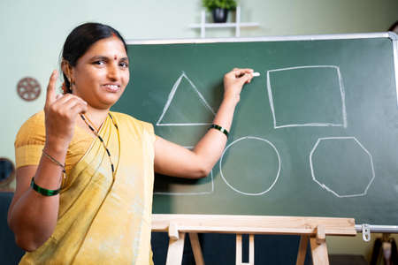 Indian woman busy explaining from board during online class by looking camera at home - Concept of e-teaching, Remote learning, virtual education during  outbreak.