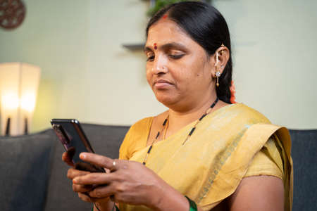 Serious Indian woman busy using mobile phone while sitting on sofa at home - Concept of social media bullying and online messaging