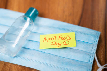 April fools day sticky note on Medical face mask with hand sanitizer bottle on table - concept of April fools day celebrations during pandemic. 免版税图像