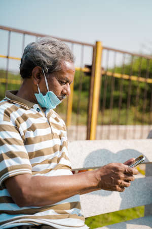 Senior man with medical face mask below the jaw using smartphone at park 免版税图像
