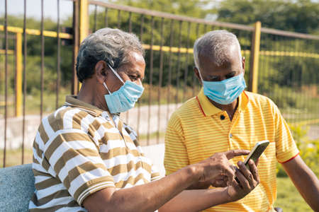Selective focus on mobile, elderly man in medical face mask showing mobile phone to his old friend at park - 免版税图像